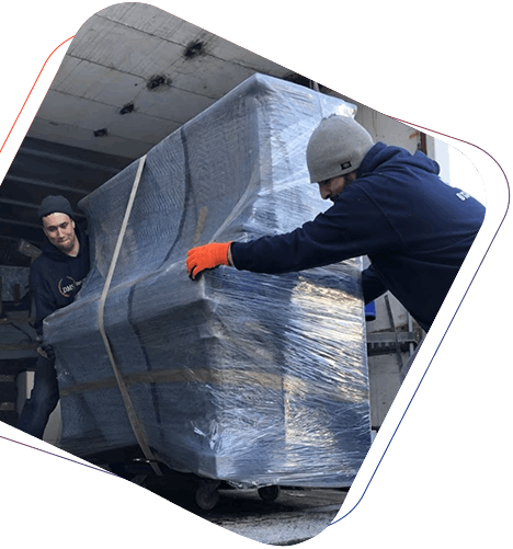 Two men moving a bubble wrapped piano in a moving truck