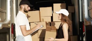 A mover giving boxes to a girl