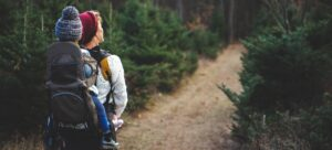 a woman hiking throught the forrest with a baby
