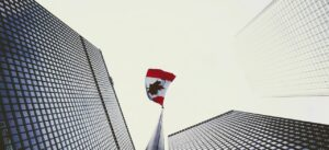 a picture looking at the top of two buildings with a canadian flag in the middle