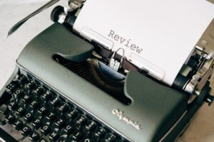A typing machine with the word 'review' written on the paper, making you want to write a moving review after your relocation