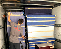Furniture wrapped in blankets in moving truck