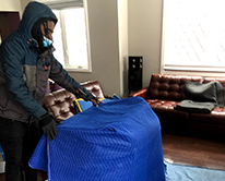Man wrapping furniture in blankets to move
