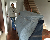 Man moving furniture wrapped in blankets