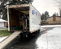 Moving truck in driveway with ramp and snow